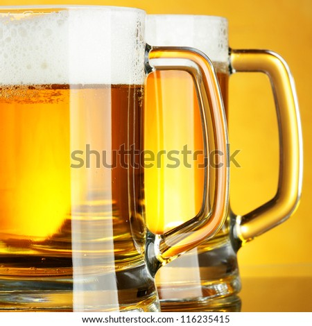 Beer mugs with froth over yellow background