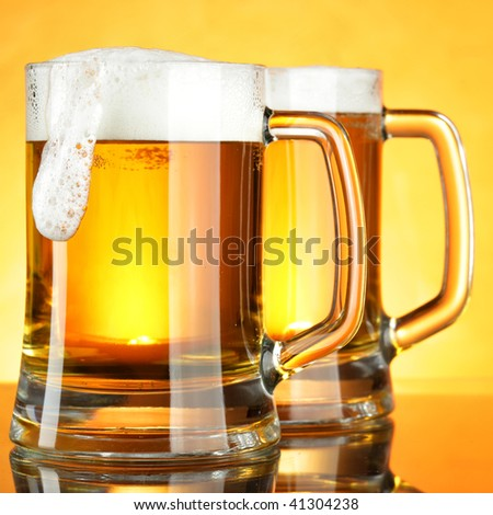 Beer mugs with froth over yellow background - stock photo