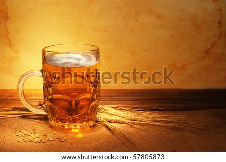 beer on sacking with wheat in ambient light  still-life - stock photo