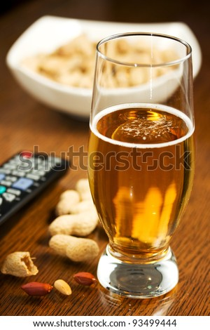 Beer, peanuts and TV remote - stock photo