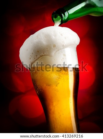Beer pouring from bottle into glass on red background - stock photo