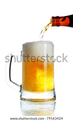 beer pouring from bottle into mug isolated - stock photo