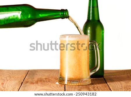 Beer pouring into a glass. Isolated on white background - stock photo