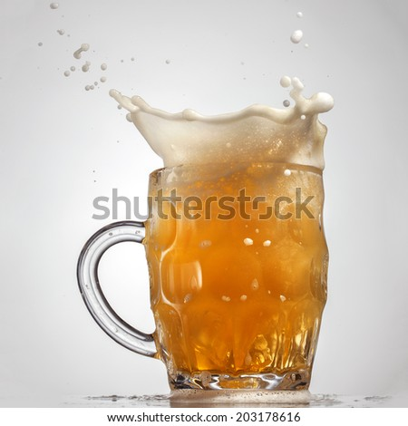 Beer splash in glass isolated on white background - stock photo