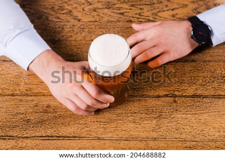 Beer time. Top view of male hands holding beer glass on the bar counter  - stock photo
