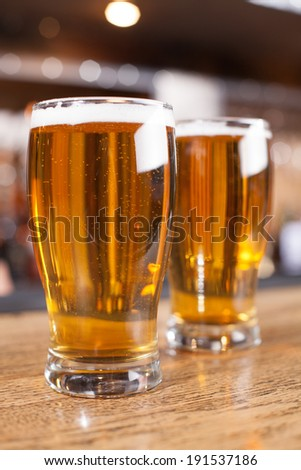 Beer.  Two glasses of beer on the wooden table in bar