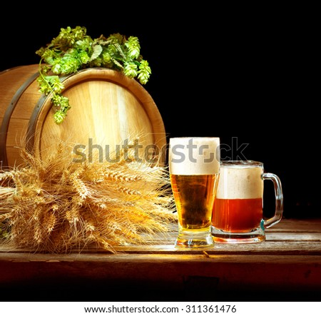 Beer. Vintage barrel and glasses full of fresh beer with hop cones and wheat of ears on wooden table isolated over black background. Brewing traditions. Ingredients for beer. Brewery concept  - stock photo