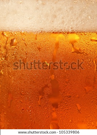 Beer with foam in cool glass taken closeup suitable as background. - stock photo