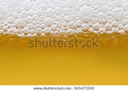 Beer with foam in transparent glass. Abstract Macro - stock photo