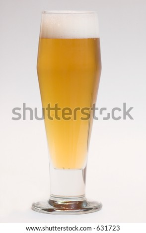 Beer with full head in beer glass - stock photo