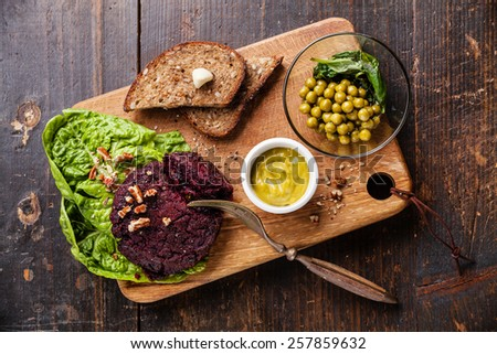 Beet cutlet vegan meatless served with green peas salad on dark wooden background - stock photo