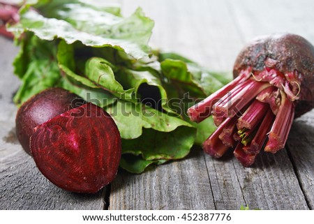 beet roots and green leaves on wooden background.