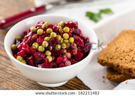 Beet salad in bowl. Russian beetroot salad with beetroot, potato, carrot, pea and oil dressing - stock photo