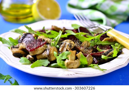 Beet salad with arugula and mushrooms on a white plate. - stock photo