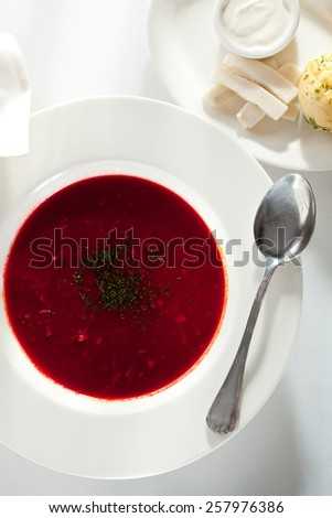 Beetroot and Cabbage Soup with Meat Slice. Garnished with Bread, Lard and Sour Cream - stock photo