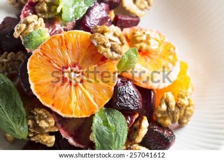 Beetroot and Orange salad with walnuts and mint leaves. - stock photo