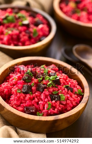 Beetroot risotto prepared with beetroot puree, roasted beetroot pieces and parsley on the top, photographed with natural light (Selective Focus, Focus in the middle of the first risotto)