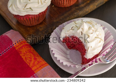 Beetroot velvet cupcakes with goat cheese cream and dried rosemary, bite, close up - stock photo