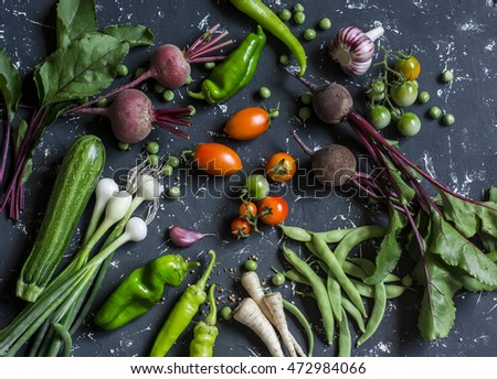 Beets, zucchini, peppers, onion, garlic, green beans, beans, tomatoes, parsnips, parsley - fresh vegetables on a dark background. Raw ingredients. Top view