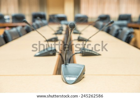 Before a conference, the microphones in front of empty chairs. Selective focus - stock photo
