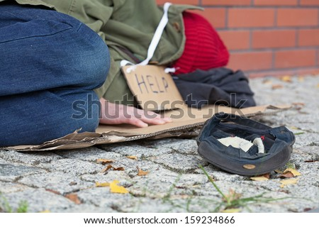 Beggar falling asleep on the street with a cap for collecting money - stock photo