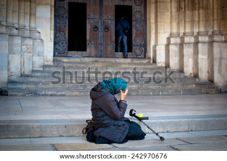 Beggar outside a church - stock photo