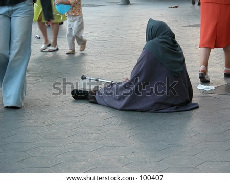 Begging woman with people walking by in the streets of Barcelona, Spain - stock photo
