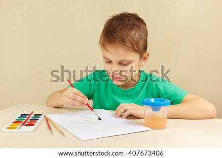 Beginner artist in a green shirt painting colors - stock photo