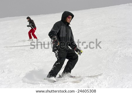 Beginner skiers coming down the slope - stock photo