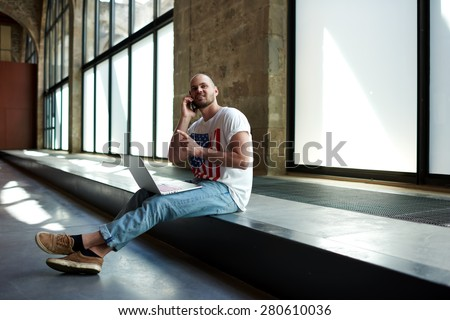 Beginning business man sitting in new premise for rent or empty work space talking on mobile phone,male interior designer or young architect sitting in empty office working on a laptop and smart phone - stock photo