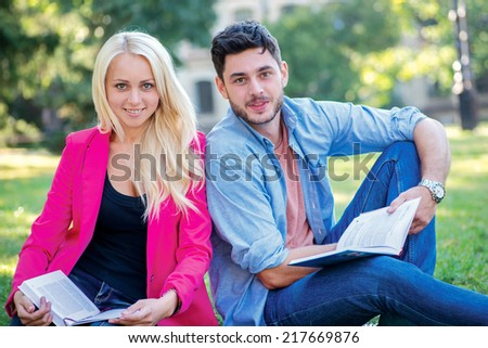 Beginning of the school year. Couple of students sitting on the grass and smiling at the camera while teaching lessons on a break near the university building - stock photo