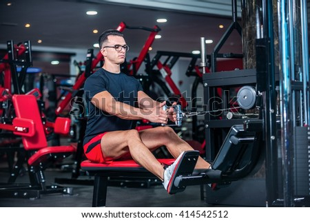 Beginning sports day. Strong athlete doing exercise at the gym. The athlete does a workout at the sports simulator. - stock photo