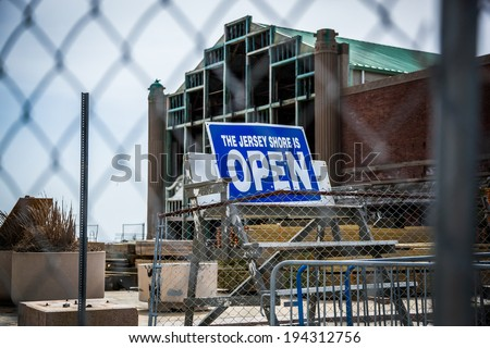 """Behind a chain link fence, a sign stands reading """"The Jersey Shore is Open."""" Photo taken in April, 2013 in Asbury Park, NJ. You can see signs of reconstruction as they rebuild from Hurricane Sandy. - stock photo"""