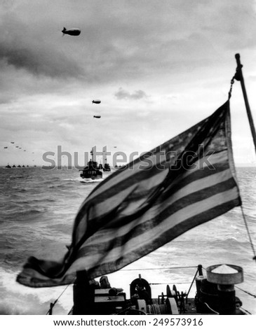 Behind an American flag, a convoy of landing craft head for Utah Beach on June 6, 1944. Each ship has barrage balloon connected by a cable during the D-Day invasion of Normandy on June 6, 1944. - stock photo
