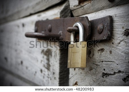 Behind the new lock and old wooden door - stock photo