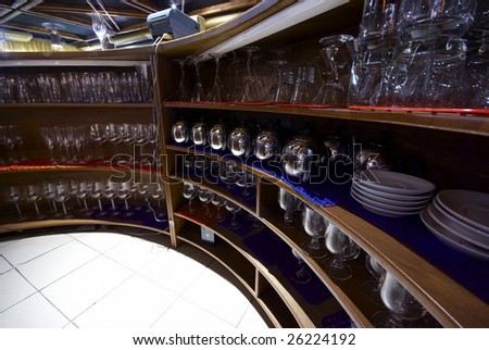 Behind the real bar counter with rows of glass - stock photo