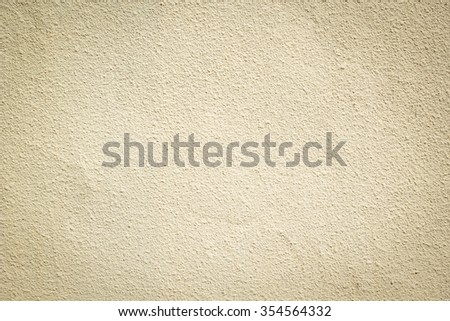 beige brown colored cement wallpaper background textured:pure cement wall backdrop for home,room,interior,design,decorate:yellow cream tone color of clean stucco.tan and vignette display concept. - stock photo