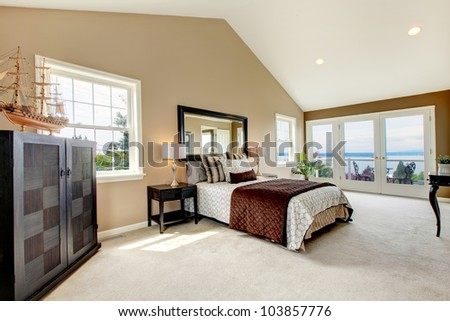 Beige classic large bedroom with water view and carpet.