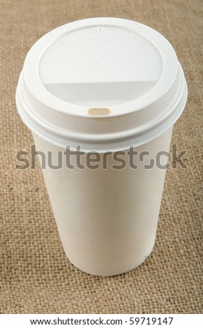Beige disposable coffee cup on canvas. - stock photo