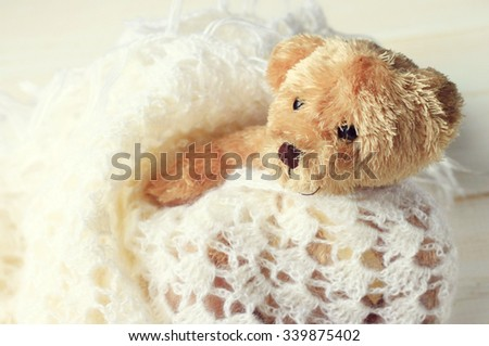 Beige fluffy cute teddy bear toy wrapped in knitted white plaid for comfort in winter. Soft focus, soft light. Toned. - stock photo