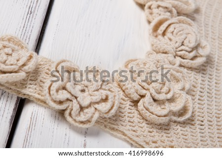 Beige knitted garment. Knitted clothes on wooden background. Lady's trendy homemade clothing. Example of durable fabric.