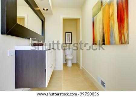 Beige modern bathroom with dark brown cabinet. - stock photo