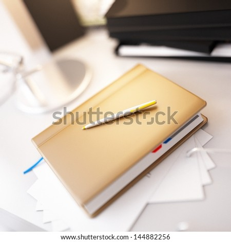 Beige personal organizer and pen on office desk - stock photo