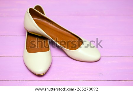 beige shoes on a pink background  - stock photo