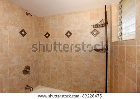 Beige stone tile shower with white tub - stock photo