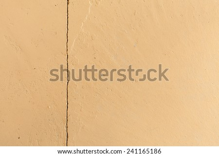 Beige texture concrete wall with vertical crack - stock photo