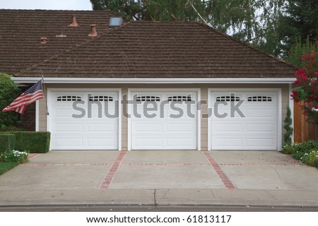 Beige three ar garage with white doors and brick and red brick driveway - stock photo