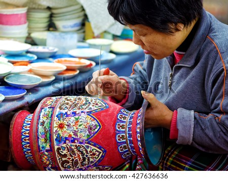 BEIJING - April 11, 2016: An artisan in China Making Cloisonne. Cloisonne is typically called the Blue of Jing Tai as blue was the dominant color used for enameling.  - stock photo
