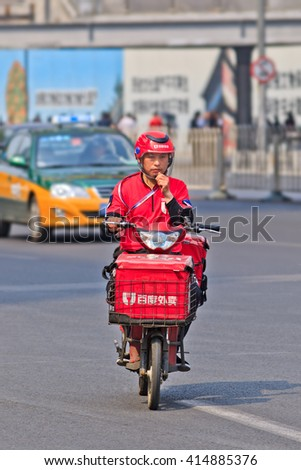 BEIJING-APRIL 28, 2016. E-bike food courier. China's growing popularity of diner delivery is the latest challenge to long-established but struggling Western companies McDonald's, KFC and Pizza Hut. - stock photo