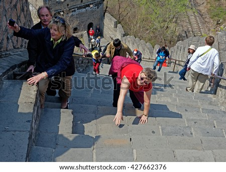 BEIJING - April 10, 2016: Tourists struggle climbing the Great Wall in China - stock photo